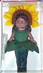Vogue Doll Company's Sunflower modern Ginny Doll is from the 2001 Botanical Baby Collection representing various flowers. She is African-American with dark moving eyes and long black hair, and she is 8 inches tall.  Her flower costume consists of a green felt leaf body suit over dark green tights with cloth green slippers. Her sunflower headdress includes felt with yellow petals over brown pompoms. How like a sunflower she is! Retired, new, and mint-in-the-box condition, with doll-sized comb and brush.