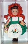 Vogue Doll Company's Little Red Riding Hood No. 1H7HP188 from the 2001 Storybook Ginny Collection. This modern Ginny Red Riding Hood doll is 8 inches tall and has green moving eyes and brunette hair. She is wearing a green jumper with white blouse and floral apron, red cape and hood, and black center-snap shoes. She is carrying a basket with a red and white checked cloth.  This discontinued doll is new, mint-in-the-box and includes a doll-sized comb and brush.