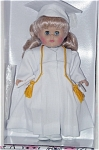 Vogue 2002 Graduation Blonde Modern Ginny doll from the Ginny Celebrates collection. This hard vinyl doll is 8 inches tall with moving blue eyes. Her ensemble includes a white dress underneath a white gown with gold tassels on hood, a white graduation cap, white tights, and white center-snap shoes. A miniature diploma and doll comb and brush are included.  Mint-in-the-box old stock.