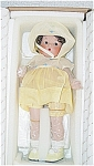 Vogue Just Me Revisited in Yellow from 2002, 10 inch doll, reproduction of 1930s forerunner of Ginny is a bisque and composition combination material, has a curly brunette mohair wig, and glass-like side glancing blue eyes. She is wearing a 1930s-style yellow organdy dress with white bodice with blue cloth rosebuds trim, yellow and white bonnet, matching yellow shoes and white socks. This same outfit is also offered on a 14 inch doll in a smaller edition. Limited edition of 1,500. Retired doll is in new and mint-in-the-box condition, and includes metal doll stand and certificate. Expand listing to view all 4 pictures.