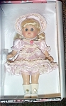 Vogue 2003 Victorian 1855 in Pink modern Ginny, No. 3HP278, 8 inch hard vinyl doll with long pale blonde hair with bangs and moving blue eyes. Her ensemble includes a pink satin dress with lace, braid trim, a pink rosebud at the neckline, and attached apron, a matching satin hat with white feathers, white socks, and white center-snap shoes, and she is carrying a matching beaded purse. She is part of the 2003 Victorian Collection. Retired doll is new and mint-in-the-box with a doll-sized comb and brush.