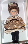Vogue 2003 Victorian 1875 (Brown) modern Ginny, No. 3HP280, is an adorable 8 inch hard vinyl doll with rooted hair styled in upswept brunette ringlets and moving blue eyes. She is wearing a satin tan dress with cameo and lace collar at neckline, matching purse and cloth hat with flowers, black stockings, and black shoes. This doll's wonderful hairdo is unique. A doll-sized comb and brush is included. Retired, new, and mint-in-the-box.