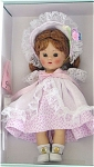 Vogue 2004 Vintage Reproduction Pink Buds inspired by Early Doll No. 7036 is a 7.5 inch hard plastic strung Ginny doll. She has a long auburn wig and bangs, moving brown eyes, and painted lashes. She is wearing a pink flower buds on white print pinafore dress with a lacy white over skirt that is open in the front, a matching lined bonnet of the same print on the outside, white on inside, with lace and pastel flower edging, white socks, and white center-snap shoes. She is carrying a pink purse that says 'Ginny' just like the old dolls had. This doll's outfit is inspired by the outfits of the 1950s Ginnys. Limited edition of 1,000. She has wonderful coloring and looks like the best of the dolls produced in 1952 and 1953. Doll is new, mint-in-the-box, includes her certificate and doll-sized comb and brush. Expand listing to view all 3 photographs.