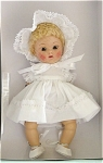 Vogue 2004 Vintage Reproduction Crib Crowd 'Baby Love' strung 7 inch sitting Ginny baby doll with bent legs. She has a short curly pale blonde lamb's wool-type wig, moving brown eyes, and painted lashes. She is wearing a white cotton dress with white cotton lace trim, matching cotton lace trimmed bloomers, cotton lace trimmed bonnet, and white lacing shoes. This doll is from a discontinued limited edition of 1,000. She has wonderful coloring and looks very much like the babies around 1951. There are currently no Crib Crowd dolls in production at Vogue Doll Company. New, mint-in-the-box and includes her certificate.