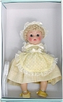 Vogue 2005 Crib Crowd Yellow Dimity doll, Limited Edition 1,000. Sitting 7 inch baby doll with pale blonde lamb's wool-type wig and brown eyes with painted lashes. Her outfit includes a pale yellow dress with dots and matching bonnet, and soft yellow shoes. Her outfit is inspired by the 1950 Crib Crowd babies, an early baby version of the Ginny dolls. There are currently no Crib Crowd dolls in production. Mint-in-the-box old stock with certificate and a doll-sized comb and brush.