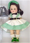 Vogue 2005 vintage reproduction 7.5 inch hard plastic Ginny doll, Hope, with brunette flip side-part hair and moving blue eyes with painted lashes. She is wearing a green gingham trimmed cotton school dress with suspenders, black bow at her neck, black belt and purse, white socks, and green center-snap shoes. This doll is based on a very popular style in the 1953 Kindergarten School Series, 'Hope' No. 27. Limited Edition 1,000.  Discontinued, new, mint-in-the-box, with certificate.