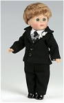 Vogue 2006 No. 6HP333 Groom doll is an 8 inch hard vinyl boy version of Ginny has dark blonde hair and moving green eyes from the Wedding collection. His wedding outfit  consists of a black tuxedo suit with a checked vest, and white flower, and tie, and black shoes. Limited edition of 350. New, mint-in-the-box with certificate and doll-sized comb and brush.