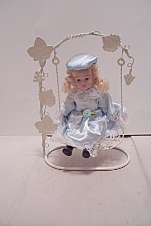 Little Blonde Haired Girl Doll In Swing (Image1)