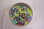 Stunning vintage Murano art glass paperweight made up of multi-colored canes sitting on a copper flake base enclosed in crystal clear glass.  2-1/4 inches in diameter and 2-1/4 inches tall.  Has Muran...