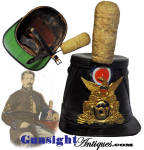 An exceptionally nice looking import leather shako complete with  original die struck brass American eagle over infantry horn plate as illustrated in Stanley Philip�s, <I> Excavated Artifacts from Battlefields & Campsites of the Civil War</I>.  All original and complete, this example even retains the chin strap with original strap retainer in the crown.  Both original features are generally long since gone.  This one even sports its period dress wool pompom.  Known to have been imported early in the Civil War the use of this handsome shako has been well established by virtue of camp site and battle field excavations with records of use by Massachusetts, Pennsylvania and New York regiments.   Offers good evidence of age and originality yet all in excellent condition with nice original finish and solid construction even to its original 2 � inch wide sweat band.  An attractive piece of Civil War head gear at a reasonable price!  <B>Buy with confidence! </B><I>  We are pleased to offer a <B><U>no questions asked</U> three day inspection with return as purchased on direct sales!</B> <I>Just send us a courtesy  e-mail to let us know your item will be returned per these provisions and your purchase price will be refunded accordingly.</I>  Thanks for visiting Gunsight Antiques !