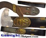 This black bridle leather belt (buff reverse) with brass keeper is set off with the retention of its dragoon style <I>puppy-paw</I> belt plate.  Of special interest to the collector will be that this dragoon plate features a scarce variation in that the <I>puppy paws</I> and hook are reversed with the <U><I>puppy paw</I> keepers on the left with the tongue on the right.</U>  The heavy bridle leather belt remains pliable and is in unusually pleasing, likely unissued, condition yet with good evidence of age and originality.  The plate like the belt remains in nice original condition and will be best evaluated by our photos.  These belted dragoon buckles are scarcely seen in this condition and serve well in any quality collection.  Superb belt & buckle collectible.   <B>Buy with confidence! </B><I>  We are pleased to offer a <B><U>no questions asked</U> three day inspection with return as purchased on direct sales!</B> <I>Just send us a courtesy  e-mail to let us know your item will be returned per these provisions and your purchase price will be refunded accordingly.</I>  Thanks for visiting Gunsight Antiques!