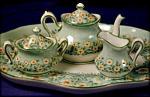 Mini Crown Staffordshire tea serving set. Porcelain. England.  c. 1920-1930.  Teapot, creamer, covered sugar & tray. Hand painted & jeweled. Pale green ground with white. Background transfer of darker...