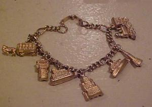 Goldtone charm bracelet w/trains, boats etc (Image1)