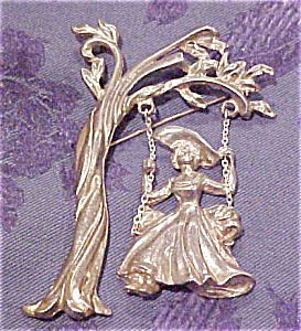 Woman in swing under tree brooch (Image1)