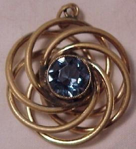 Swirling gold filled pendant with sparkling light blue centerstone. (Image1)