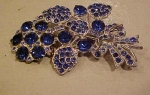 Flower pin with blue rhinestones.