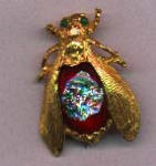 Goldtone bug pin with red glass body and multicolored center in the glass