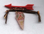 Plastic Native American motif pin w/arrow and leather