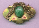 Brass sash ornament with green glass cabachon.