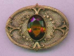 Sash ornament brooch with topaz glass centerpiece.