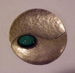 Hammered silver pin with green glass stone