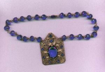 Czechoslovakian blue faceted glass bead necklace with large brass pendant with blue rhinestones