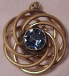 Swirling gold filled pendant with sparkling light blue centerstone.