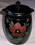 Beautiful old cookie jar made of black amethyst glass. It has a red rose hand painted on the front.<BR>Green leaves and a bud ready to pop open makes a striking decoration. Very minor wear to the<BR>h...