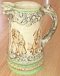 Featured for your enjoyment is a stunning old milk pitcher. The spout is shaped like aface on the end of a tree trunk. The rim has leaves and some sort of fruit. There appears tobe a scene that is fro...