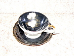 Click here to enlarge image and see more about item blackwhitecup: Black and White Flowered 3 legged Cup &Saucer