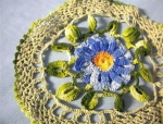 Click here to enlarge image and see more about item 06200231: Hand Crocheted Doiley with Blue Flower.