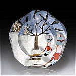 "A boy pulls a sled over a snow-covered ground beneath a bird perched in a wintery leafless tree.  Five and one facets; signature cane. LE of 200. Diameter: 2 ¾""."