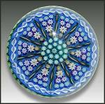 "Perthshire: Patterned millefiori and twist cane paperweight. An attractive early Perthshire paperweight in shades of blue and green. It has a central ""P"" cane, surrounded by two concentric r..."