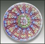 Early concentric millefiori paperweight with 11 radial twist canes dividing groups of canes that radiate from a central cluster. This vividly-colored Perthshire design is set on an opaque red ground ...