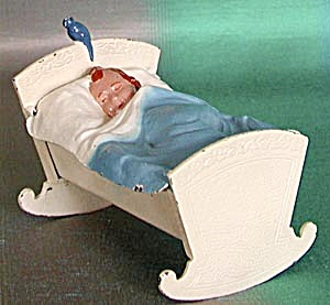 Cast Iron Baby in Cradle with Bird on Headboard Bank (Image1)