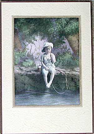 Boy Sitting On A Bank Fishing