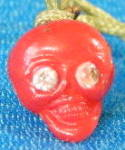 Click here to enlarge image and see more about item CHU29: Vintage Red Celluloid Skull w/ Rhinestone Eyes Charm