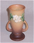 This is a  circa 1950 Roseville vase made in the Gardenia pattern.  The color is golden tan with a matte glaze. It is marked with Roseville U.S.A. in relief and the style number 682-6. It measures 6 ¼...