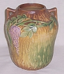 This is a circa 1937 Roseville vase made in the Wisteria pattern. The color is a brown textured background blending into a dark green, with lavender wisteria blossoms and a satin matte glaze. It is un...