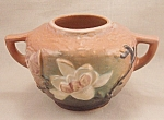 This is a circa 1943 Roseville bowl made in the Magnolia pattern. The background color is terra cotta blended with green with a matt glaze. The bowl is marked with a raised Roseville U.S.A. and the s...