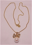 COSTUME JEWELRY - ANNE KLEIN LONG GOLD TONE NECKLACE WITH BOW AND PEARL PENDANT