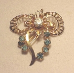 Click to view larger image of VINTAGE COSTUME JEWELRY - BLUE RHINESTONE GOLD TONE BOW BROOCH OR PENDANT (Image1)