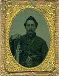 Ninth plate tintype of a Union soldier wearing a shell jacket, over the shoulder leather belt, rectangular eagle belt plate, a Colt pistol is prominently displayed tucked inside of his belt and he holds a cavalry saber at his side. Comes in a full leather covered case with red velvet liner, brass mat, keeper and glass. Very fine double armed Yankee cavalryman.
