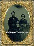 """Quarter plate tintype of a Union officer posing with his wife and son. The officer, at the left, is wearing a frock coat with shoulder straps, vest and tie. His son, at the center, is wearing a zouave style jacket, while his wife, at the right, is holding a thermoplastic image case in her hand. There is a small dark spot in the emulsion at the upper edge of the image. This does not affect the subjects. Comes with brass mat, keeper and glass, and is displayed in a full thermoplastic case with green velvet liner. Although the case looks like it has been together for the past 150 plus years, as I can see no sign of repair on the riveted hinges, it is a mismatched case with two very scarce themes, one on each half of the case. One half has the theme titled, """"Cupid and the Wounded Stag."""" [Krainik #36]. Casemaker: Littlefield, Parsons and Company. Quarter plate, 4 7/8 x 4. The center design on this case suggests that Love (Cupid) has conquered the male heart (the stag). Although this design suggests a classical or mythological allusion, we have been unable to locate a source illustration. The other half of the case has the design titled, """"The Music Lesson."""" [Krainik #37]. Die engraver: Anthony Schaefer. Casemaker: Littlefield, Parsons and Company. Quarter plate, 4 7/8 x 4. The central design on this case shows three figures in eighteenth century dress. The young woman seated at the harpsichord is receiving musical instruction from a gentleman beside her. Another musician stands slightly behind the pupil and takes apparent interest in her progress. A small stringed instrument leans against a chair in the background. The origin of this case has not been located. It may have first appeared as an engraving in one of the numerous periodicals of the mid-nineteenth century. An imprint inside of the case identifies it as having been made by Littlefield, Parsons & Co., with 1856 & 1857 patent dates. Since both of these designs were made by the same casemaker, Littlefield, Parsons """